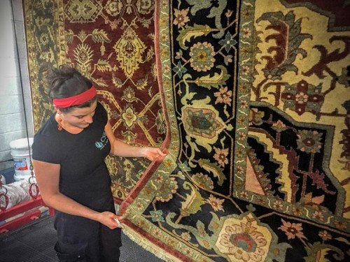 Woman hanging and drying an Oriental rug in Cardiff