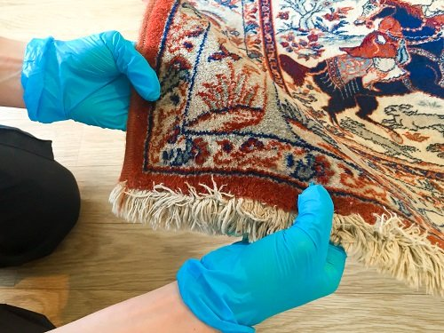 Close up inspection of a Persian rug in Cardiff
