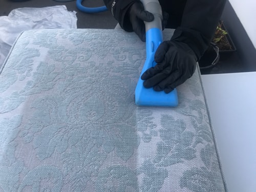 Cleaning a fabric cushion using a upholstery tool in Cardiff